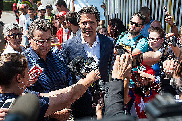 Fernando Haddad (center), who replaced ex-president Lula as the Workers' Party presidential candidate, speaks to journalists