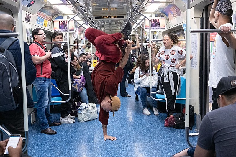 Mesmo com o trem em movimento, dançarinos de hip hop se apresentam em meio aos passageiros