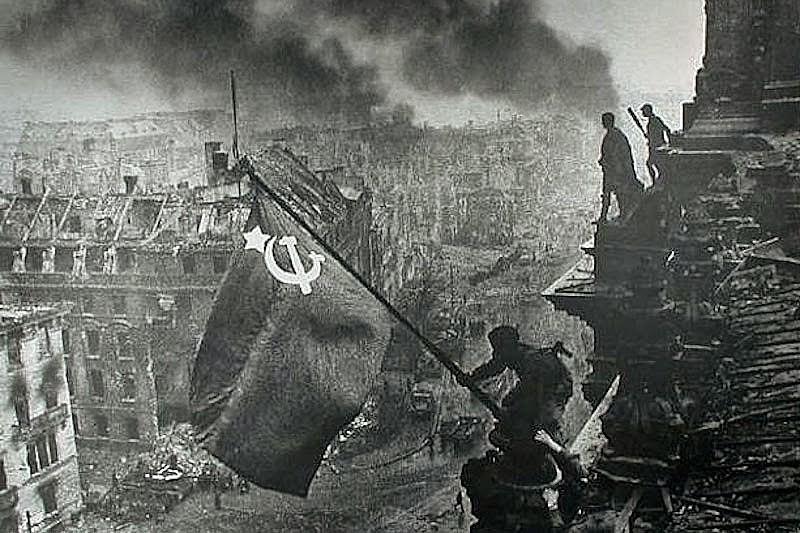 Soldado hasteia bandeira soviética no telhado do Reichstag, a sede do Parlamento alemão, em 9 de maio de 1945