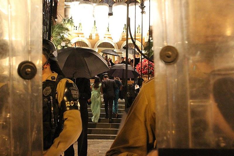 Convidados da festa usaram guarda-chuvas como escudo de proteção contra ovos arremessados pelos manifestantes