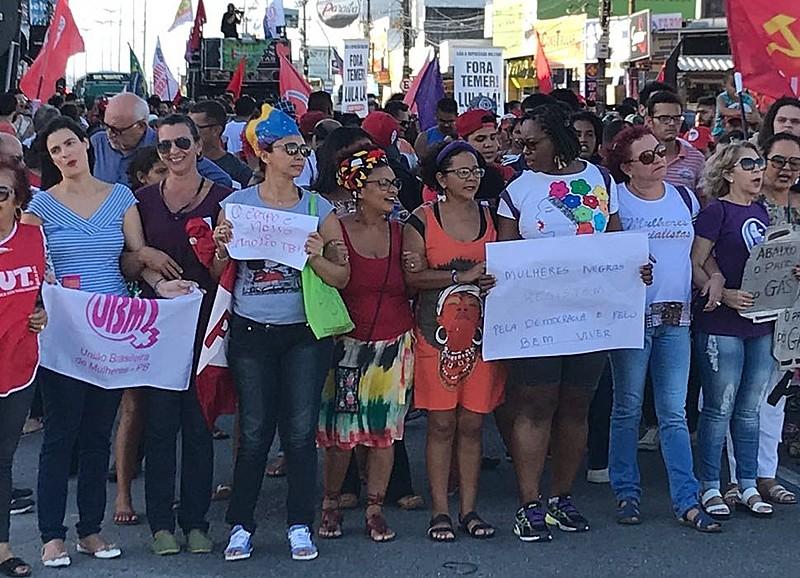 """A frente do ato as mulheres seguravam cartazes e replicas de botijão de gás com os dizeres """"O petróleo é nosso"""" e """"abaixo o preço do gás""""."""