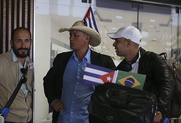 """Profissionais embarcaram com bandeiras de Cuba e do Brasil e com adesivos com a mensagem """"Somos mais que médicos"""""""