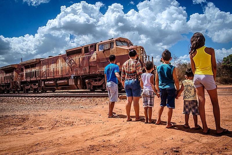 Família a espera que o trem, carregado de minério, passe para atravesar