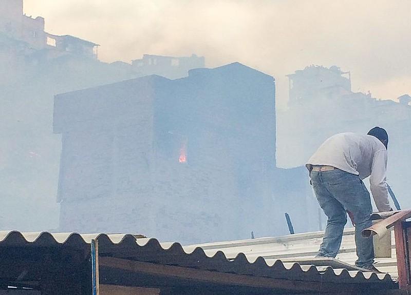 Morador tenta combater o fogo na favela de Paraisópolis