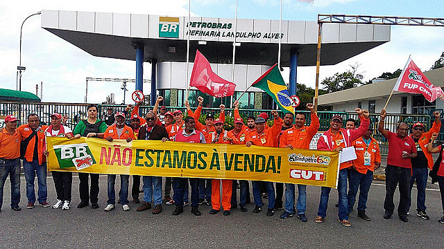 """Oil workers stand against privatization of state-owned oil giant Petrobras. The banner reads """"We're not for sale"""""""