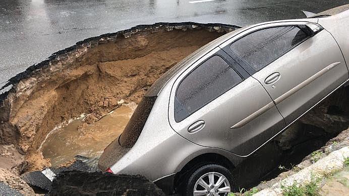 Carro engolido por buraco provocado pelas chuvas, no Bairro dos Estados, em João Pessoa (PB)