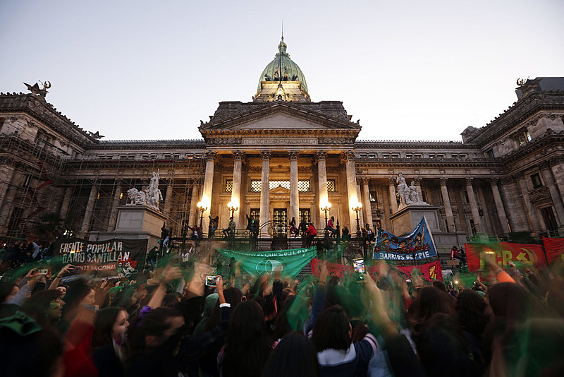 Manifestantes levantam seus lenços verdes, símbolo da campanha pelo aborto legal, em frente ao Congresso argentino