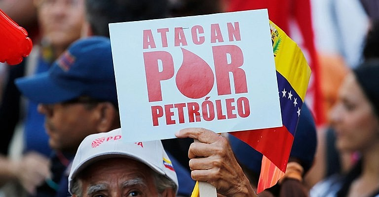 """Manifestante segura uma placa onde se lê """"Atacam por petróleo"""" durante um protesto em apoio a PDVSA em Caracas"""