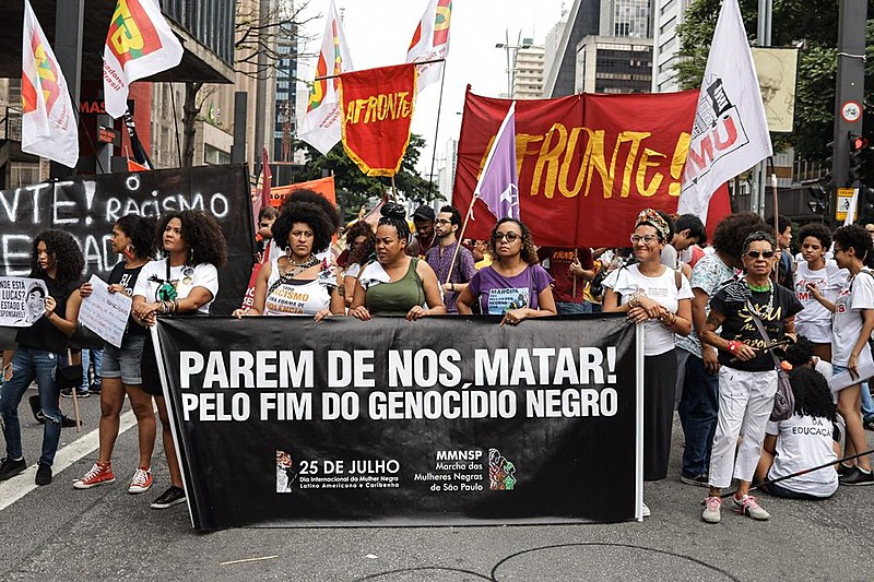 "Marchers hold banner that reads ""Stop killing us! For the end of black genocide"" during demonstration in São Paulo on Nov. 20"