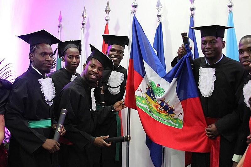 Formandos comemoram ao lado da bandeira do Haiti