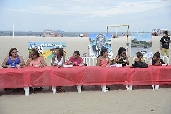 Mesa coberta por uma toalha vermelha simbolizando o sangue das vítimas foi estendida na areia