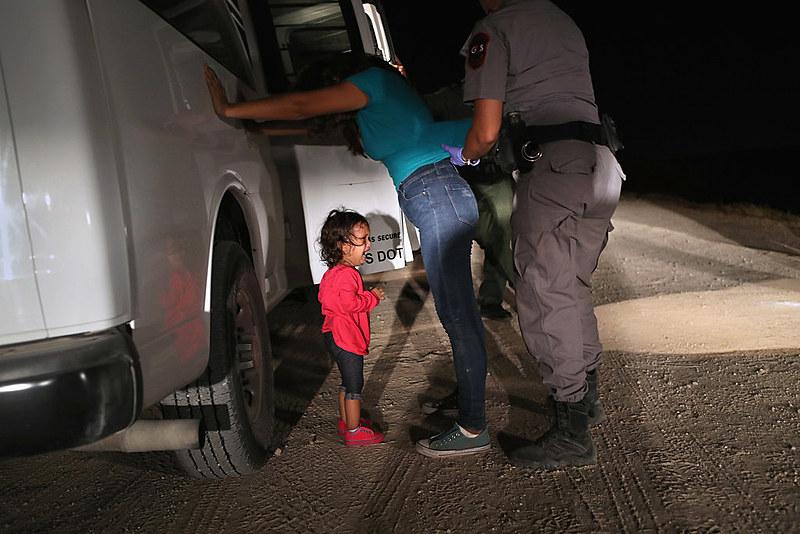 Imagem de criança chorando ao ver sua mãe ser revistada por uma agente de segurança dos EUA se tornou símbolo da perversa política de Trump