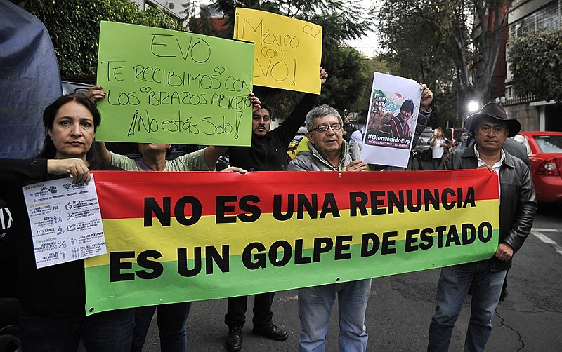 People demonstrate in support of Evo Morales, holding a banner that reads 'It's not a resignation, It's a coup', in Mexico City on Nov. 11