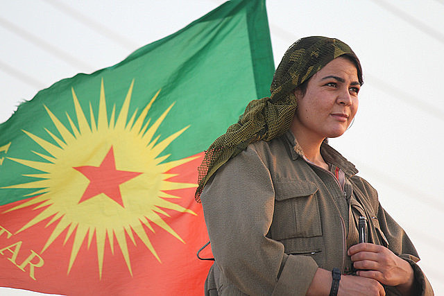 Kurdish fighter with PKK flag; taking down the patriarchy is crucial for the party to end the war