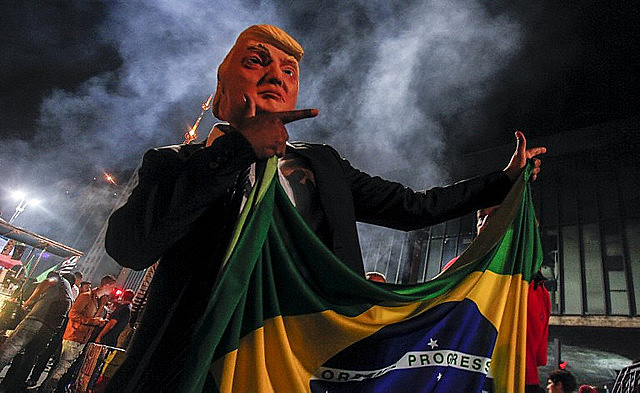 """A Trump doll holds the Brazilian flag and does Jair Bolsonaro's signature """"guns up"""" hand gesture"""